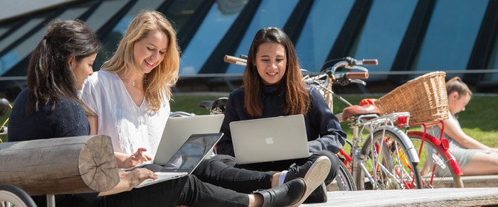Three students with laptops, sitting in the sun and talking